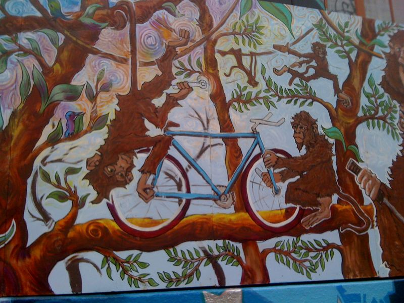 Street art monkeys repairing bicycle